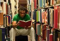 person in a library holding a book 300x206