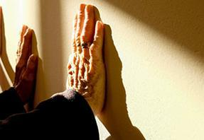 Elderly clients hands against wall