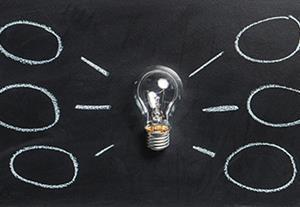 Light bulb on chalk board with speech bubbles